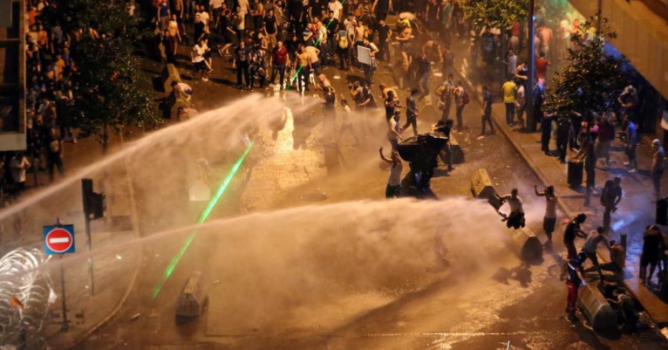 Lebanese activists shout 'Revolution! Revolution!' as they are sprayed by riot police using water cannons Sunday evening in Beirut, Lebanon, Aug. 23, 2015. (AP photo)