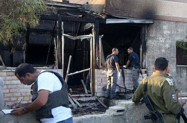 Security forces inspect the West Bank house destroyed in an arson attack on July 31, 2015. (AFP/Jaafar Ashtiyeh)