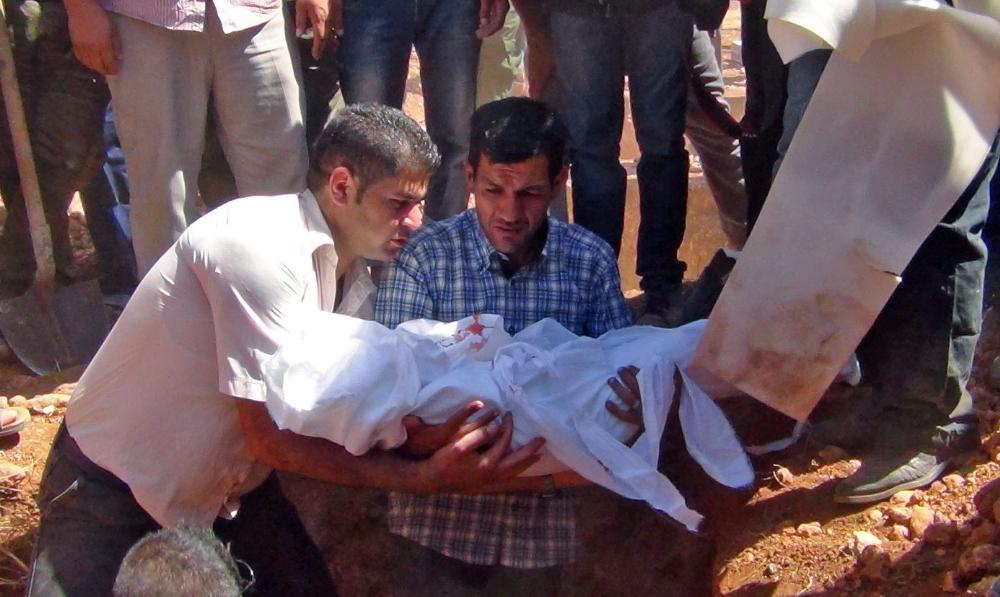 Abdullah Kurdi (center), father of the drowned three-year-old boy, holds his son's body during the funeral in Kobane. Photo via Dicle News Agency/EPA