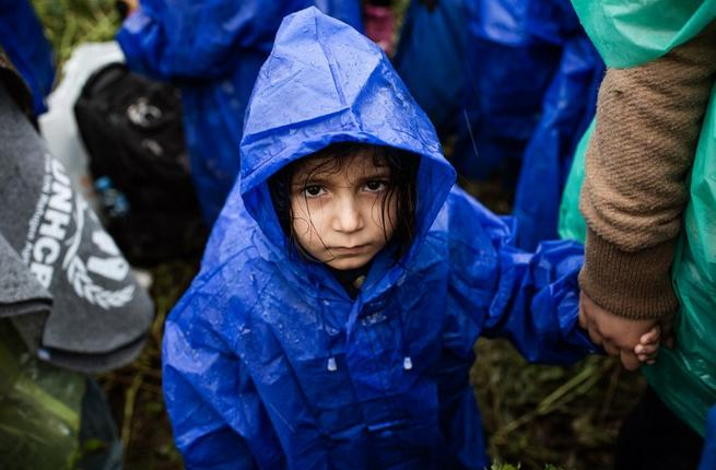 A child waits in the rain on the Serbia-Croatia border, October 19, 2015. (AFP/File)