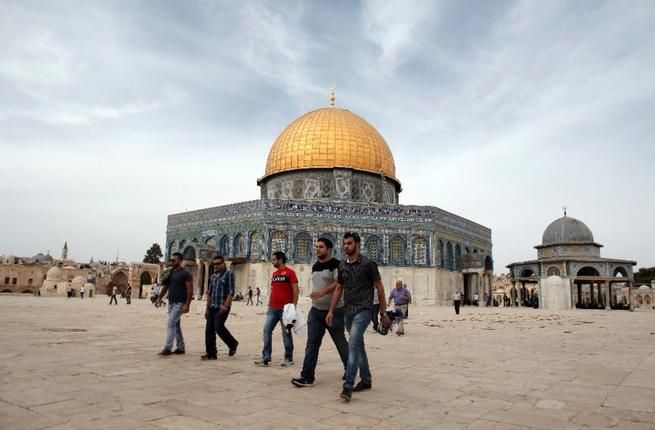 Palestinian men walk past the Dome of the Rock in the Al-Aqsa Mosque compound in Jerusalem on October 23, 2015. (AFP/Ahmad Gharabli)