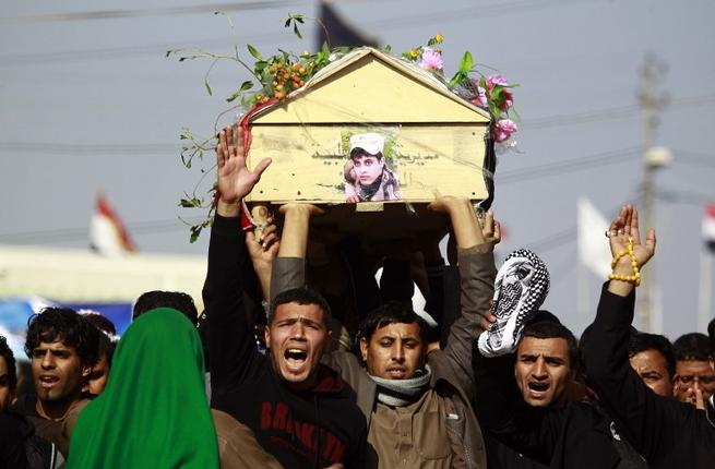 Iraqi mourners carry the body of one of the soldiers who were killed the previous day in a so-called friendly fire from a US-led coalition aircraft west of Baghdad, on December 19, 2015 during a funeral in the Shia holy city of Najaf. (AFP/Haidar Hamdani)