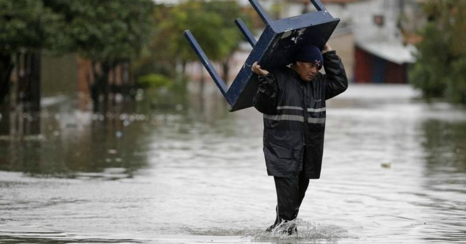 A man wades through floodwater in Paraguay. (Photo: AP)