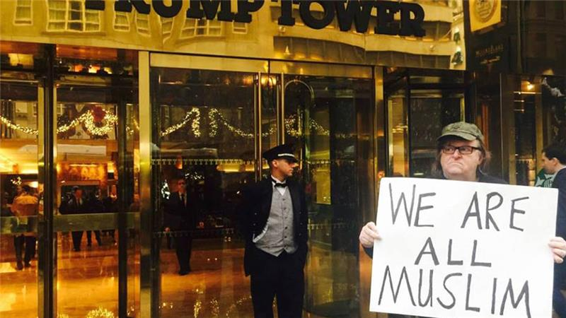 "Michael Moore holding ""we are all Muslim"" sign in front of Trump Tower in New York city."