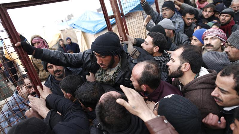 Syrian refugees wait for food near a refugee camp in Bab Al-Salama city, in northern Syria, on February 6 [Sedat Suna/EPA]