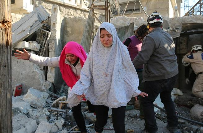 Syrian girls react following a reported Syrian regime air strike in a rebel-controlled area in the northern city of Aleppo on February 8, 2016. (AFP/Ameer al-Halbi)
