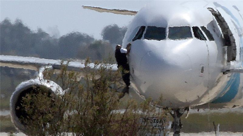 A man climbs out of the cockpit window of the hijacked EgyptAir plane at Larnaca airport [Yiannis Kourtoglou/Reuters]