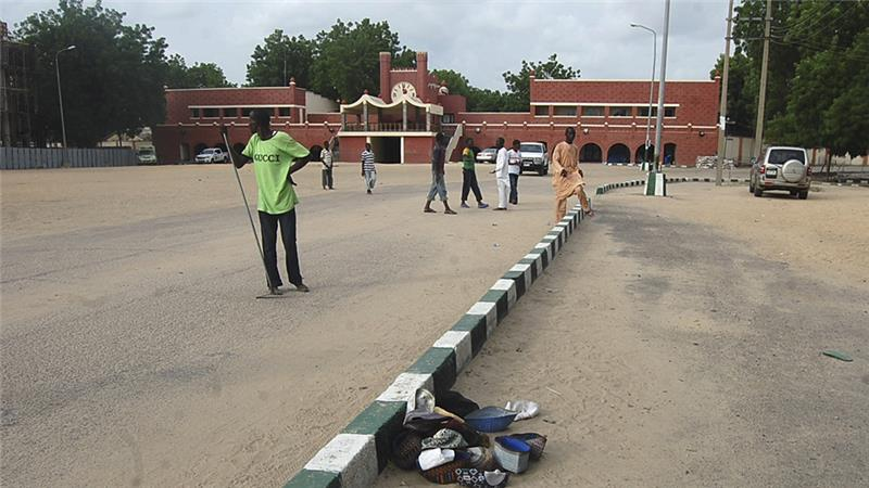 People walk in front of a mosque after a bomb attack in Maiduguri in 2012 [File: Olatunji Omirin/Reuters]
