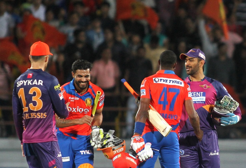 Rajkot: Gujarat Lions' Ravindra Jadeja and Dwayne Bravo with Rising Pune Supergiants captain MS Dhoni after winning the IPL match between Rising Pune Supergiants and Gujarat Lions at Saurashtra Cricket Association Stadium in Rajkot on April 14, 2016. (Photo: Surjeet Yadav/IANS)