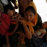Rohingya refugee women sit inside their home at a refugee camp in Bangladesh [Mohammad Ponir Hossain/Reuters]