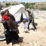 A Palestinian family, whose house was demolished by Israeli bulldozers, walk past a tent on April 21, 2015 in the southern West Bank. (AFP/File)